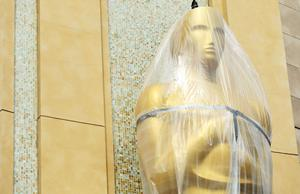 An Oscar statue is covered in plastic as preparations are made for the 86th Academy Awards