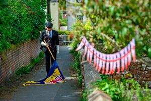 Royal British Legion standard bearer Richard Hignett lowers the standard during the two minutes' silence outside his home in Royal Wootton Bassett, Wiltshire, while remain socially distanced, during a day of events to mark the 75th anniversary of VE Day. PA Photo. Picture date: Friday May 8, 2020. Although large-scale public events are unable to go ahead because of coronavirus restrictions, tributes are being be paid by politicians and members of the royal family, as well as through a host of other events as the nation remembers those who fought and died in the Second World War. See PA story MEMORIAL VE. Photo credit should read: Ben Birchall/PA Wire