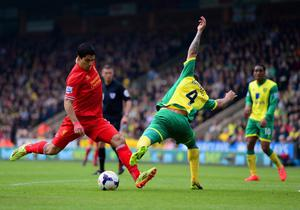 NORWICH, ENGLAND - APRIL 20:  Luis Suarez of Liverpool is challenged by Bradley Johnson of Norwich City during the Barclays Premier League match between Norwich City and Liverpool at Carrow Road on April 20, 2014 in Norwich, England.  (Photo by Jamie McDonald/Getty Images)
