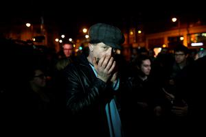 LONDON, ENGLAND - JANUARY 11: A man performs a David Bowie song on the mouth organ as people gather to celebrate his life at a gathering in Brixton on January 11, 2016 in London, England. British music and fashion icon David Bowie died earlier today at the age of 69 after a battle with cancer. (Photo by Carl Court/Getty Images)