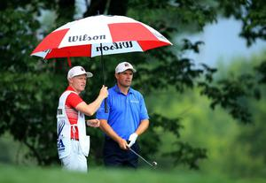 LOUISVILLE, KY - AUGUST 08:  Padraig Harrington of Ireland waits under an umbrella alongside caddie Ronan Flood before hitting his tee shot on the 11th hole during the second round of the 96th PGA Championship at Valhalla Golf Club on August 8, 2014 in Louisville, Kentucky.  (Photo by David Cannon/Getty Images)
