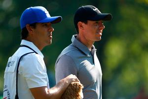 Rory McIlroy and caddie Harry Diamond look on during the first round of the World Golf Championships.