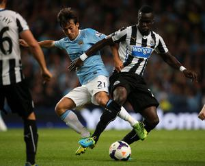 MANCHESTER, ENGLAND - AUGUST 19:  David Silva of Manchester City in action with Cheik Tiote of Newcastle United during the Barclays Premier League match between Manchester City and Newcastle United at the Etihad Stadium on August 19, 2013 in Manchester, England.  (Photo by Clive Brunskill/Getty Images)