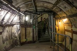 LONDON, ENGLAND - APRIL 13: A member of staff from the 'London Transport Museum' walks down a stairway in the Down Street underground station on April 13, 2016 in London, England. London Transport Museum will be giving tours as part of their new 'Hidden London' season beginning May 7, 2016. Down Street station in Mayfair operated between 1907 and 1932 and after closing, played an important part during the Second World War when it was transformed into the Railway Executive Committee's bomb proof shelter. During the height of the Blitz, British Prime Minister Winston Churchill took refuge in the station tunnels.  (Photo by Dan Kitwood/Getty Images)