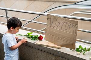 MUNICH, GERMANY - JULY 23: A small boy places a candle outside the OEZ shopping center the day after a shooting spree left nine victims dead on July 23, 2016 in Munich, Germany. According to police an 18-year-old German man of Iranian descent shot nine people dead and wounded at least 16 before he shot himself in a nearby park. For hours during the spree and the following manhunt the city lay paralyzed as police ordered people to stay off the streets. Original reports of up to three attackers seem to have been unfounded. The shooter's motive is so far unclear. (Photo by Joerg Koch/Getty Images)