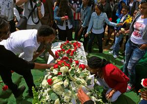 BALTIMORE, MD - APRIL 27:  Friends and relatives lay flowers on and kiss Freddie Gray's casket before it is lowered into the ground at the Woodland Cemetery April 27, 2015 in Baltimore, Maryland. Gray, 25, was arrested for possessing a switch blade knife April 12 outside the Gilmor Homes housing project on Baltimore's west side. According to his attorney, Gray died a week later in the hospital from a severe spinal cord injury he received while in police custody.  (Photo by Chip Somodevilla/Getty Images)