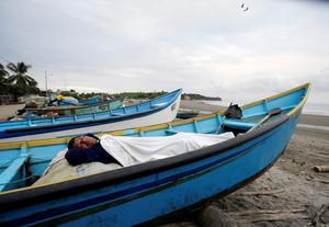 A man, his home destroyed by a 7.8 magnitude earthquake, sleeps in his uncle's boat docked along the shore, in La Chorrera, Ecuador, Monday, April 18, 2016. The Saturday night quake left a trail of ruin along Ecuadors normally placid Pacific Ocean coast. At least 350 people died and thousands are homeless. President Rafael Correa said early Monday that the death toll would surely rise, and in a considerable way. (AP Photo/Dolores Ochoa)