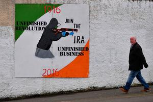 A man walks past a Republican mural in the Bogside area of Derry on March 22, 2017.