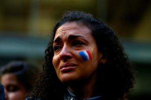 SYDNEY, AUSTRALIA - NOVEMBER 14:  A woman with a French flag painted in her face cries during a vigil for victims of the Paris terror attacks at Martin Place on November 14, 2015 in Sydney, Australia. At least 120 people have been killed and over 200 injured, 80 of which seriously, following a series of terrorist attacks in the French capital.  (Photo by Daniel Munoz/Getty Images)