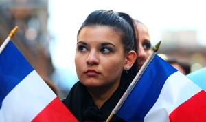 SYDNEY, AUSTRALIA - NOVEMBER 14:  A woman hold French flags during a vigil for victims of the Paris terror attacks at Martin Place on November 14, 2015 in Sydney, Australia. At least 120 people have been killed and over 200 injured, 80 of which seriously, following a series of terrorist attacks in the French capital.  (Photo by Daniel Munoz/Getty Images)