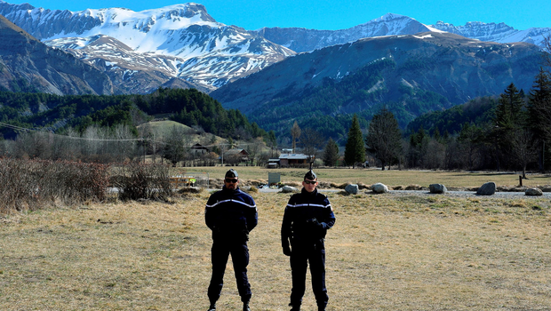 LE VERNET, FRANCE - MARCH 28:  Policemen stand in front of a memorial stone for the victims of the Germanwings Airbus flight near to the crash site on March 28, 2015 in Le Vernet, France.