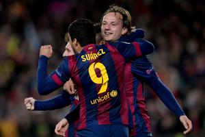 Barcelona's Croatian midfielder Ivan Rakitic (R) is congratulated by his teammate Barcelona's Uruguayan forward Luis Suarez during the UEFA Champions League round of 16 football match FC Barcelona vs Manchester City at the Camp Nou stadium in Barcelona on March 18, 2015. AFP PHOTO/ JOSEP LAGOJOSEP LAGO/AFP/Getty Images