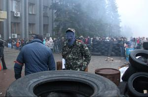 Pro-Russian activists use tires to make barricades in front of the city government headquarters in Makeyevka, about five kilometers (about 3 miles) from Donetsk, Ukraine, Sunday, April 13, 2014. (AP Photo/Alexander Ermochenko)
