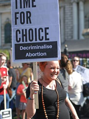 A pregnant woman holds a sign outside Belfast City Hall (Niall Carson/PA)