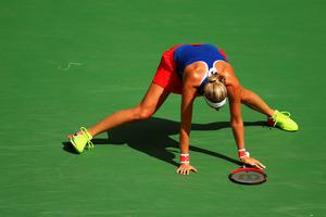 RIO DE JANEIRO, BRAZIL - AUGUST 12:  Petra Kvitova of the Czech Republic stumbles during a point against Monica Puig of Puerto Rico during the Women's Singles Semifinal on Day 7 of the Rio 2016 Olympic Games at the Olympic Tennis Centre on August 12, 2016 in Rio de Janeiro, Brazil.  (Photo by Clive Brunskill/Getty Images)