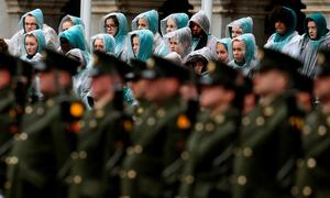 Members of a choir look on as members of the defence forces form a guard of honour during the first major event to mark the centenary of the 1916 Rising, at Dublin Castle in Ireland. PRESS ASSOCIATION Photo. Picture date: Friday January 1, 2016. Three flags which were flown on O'Connell Street during the rebellion were raised over Dublin Castle in the ceremony attended by President Michael D Higgins, Taoiseach Enda Kenny and Tanaiste Joan Burton. See PA story POLITICS Rising Ireland. Photo credit should read: Brian Lawless/PA Wire