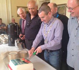 Councillor Andrew Muir cutting the cake that was produced by another bakery after Asher's Baking Company refused