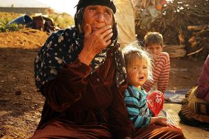 A woman and child who recently arrived from the besieged Syrian city of Aleppo pause in a makeshift camp in the Bekaa Valley, close to the border with Syria on November 11, 2013 in Majdal Anjar, Lebanon. Photo by Spencer Platt