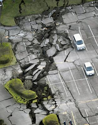 In this aerial photo, a parking lot is seen damaged by the earthquake in Minamiaso town, Kumamoto prefecture, southern Japan Saturday, April 16, 2016. A powerful earthquake struck southern Japan early Saturday, barely 24 hours after a smaller quake hit the same region.(Muneyuki Tomari/Kyodo News via AP) JAPAN OUT, MANDATORY CREDIT