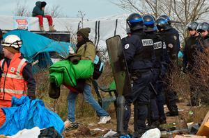 "A man carrying belongings walks past a man sitting on a shelter's roof next to anti-riot policemen as agents dismantle shelters on February 29, 2016 in the ""jungle"" migrants and refugees camp in Calais, northern France.  A French court on February 25 gave the green light to plans to evacuate hundreds of migrants from the southern half of the sprawling camp in the port town, with many wanting to stay near the entrance to the Channel Tunnel, the gateway to their ultimate goal of Britain. AFP PHOTO / PHILIPPE HUGUENPHILIPPE HUGUEN/AFP/Getty Images"