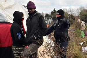 "An anti-riot policeman gestures as he speaks to a migrant while agents dismantle shelters on February 29, 2016 in the ""jungle"" migrants and refugees camp in Calais, northern France.  A French court on February 25 gave the green light to plans to evacuate hundreds of migrants from the southern half of the sprawling camp in the port town, with many wanting to stay near the entrance to the Channel Tunnel, the gateway to their ultimate goal of Britain. AFP PHOTO / PHILIPPE HUGUENPHILIPPE HUGUEN/AFP/Getty Images"