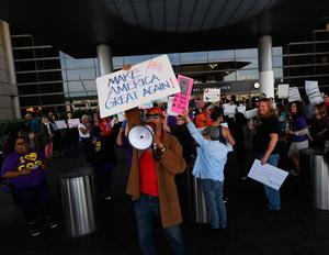 A pro-Trump supporter stands in front of a protest against the immigration ban  at the Los Angeles International Airport, California on January 30, 2016. Trump's executive order suspended the arrival of all refugees for at least 120 days, Syrian refugees indefinitely -- and bars citizens from Iran, Iraq, Libya, Somalia, Sudan, Syria and Yemen for 90 days.  Protests are taking place at airports across the country in opposition to the ban. / AFP PHOTO / Mark RALSTONMARK RALSTON/AFP/Getty Images