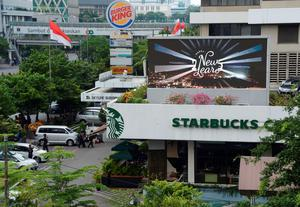 "Indonesian police secure the area outside a damaged Starbucks coffee shop after a series of explosions hit central Jakarta on January 14, 2016. Gunfire and explosions in the Indonesian capital Jakarta killed at least four people on January 14 in what the country's president dubbed ""acts of terror"", with fears that militants were still on the run. Starbucks announced in a statement that the company was closing all of its Jakarta branches ""until further notice"" after one of its stores in the Indonesian capital was hit by apparent suicide attacks.      AFP PHOTO / ROMEO GACADROMEO GACAD/AFP/Getty Images"