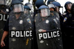 BALTIMORE, MD - APRIL 27: Baltimore Police officers in riot gear look toward protestors along Reisterstown Road near Mondawmin Mall, April 27, 2015 in Baltimore, Maryland. A group of young protestors clashed with police in the streets near Mondawmin Mall in the afternoon following Freddie Gray's funeral. (Drew Angerer/Getty Images)