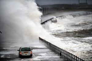 A car drives along Seaview road as waves crash over the promenade on December 9, 2014 in Saltcoats ,Scotland. The Met Office has issued a yellow weather warning for the next forty eight hours as high winds start to build ahead of an Atlantic storm due tomorrow.  (Photo by Jeff J Mitchell/Getty Images)