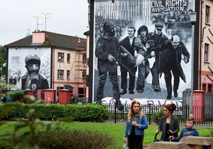 LONDONDERRY, NORTHERN IRELAND - AUGUST 11: A family walks past a mural depicting a scene from Bloody Sunday as final preparations for the funeral of the late retired Bishop of Derry, Dr. Edward Daly as he lies in state at St. Eugene's Cathedral on August 11, 2016 in Londonderry, Northern Ireland. The iconic image of the then Fr Daly waving a hankerchief over one of the Bloody Sunday victims became one of the most enduring images of the Troubles in Northern Ireland. Bishop Daly who has been described as a fearless peace-builder passed away at the age of 82 following a brief illness, he will be buried this afternoon in the grounds of the cathedral following requiem mass. (Photo by Charles McQuillan/Getty Images)