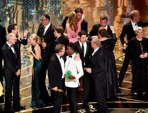 HOLLYWOOD, CA - FEBRUARY 28:  (L-R) Best Picture winner 'Spotlight' cast and crew including actress Rachel McAdams, producer Michael Sugar, director Tom McCarthy, screenwriter Josh Singer and actor Michael Keaton, actor Liev Schreiber, and host Chris Rock (C) celebrate onstage during the 88th Annual Academy Awards at the Dolby Theatre on February 28, 2016 in Hollywood, California.  (Photo by Kevin Winter/Getty Images)