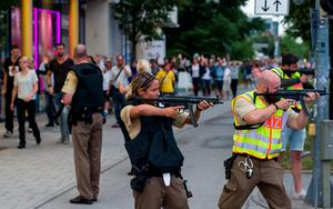 Police officers guard with guns as other officers escort people from inside the shopping center as they respond to a shooting at the Olympia Einkaufzentrum (OEZ) at July 22, 2016 in Munich, Germany.  (Photo by Joerg Koch/Getty Images)
