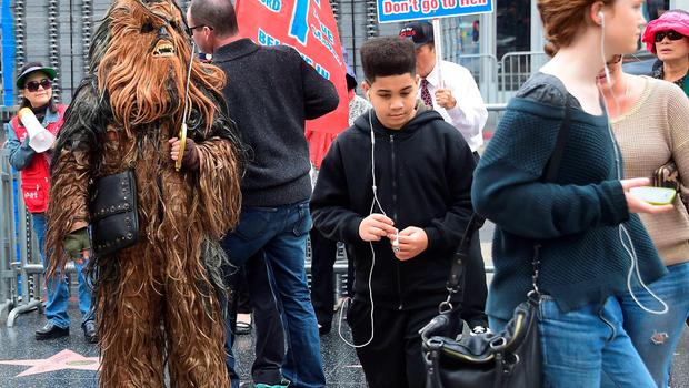 """Bystanders watch as a person dressed in a Chewbacca costume walks near where fans have been congregating at the plaza in front of the TCL Theater  in Hollywood, California on December 10, 2015, where over 100 fans with tickets in their possession and some camped out for the past three or four nights,  have been gathering in anticipation for the new film, 'The Force Awakens', which opens on December 17. Excitement over the latest """"Star Wars"""" movie is building to fever pitch as fans literally count the days, hours and minutes before the latest installment of the space saga hits screens. AFP PHOTO/ FREDERIC J. BROWNFREDERIC J. BROWN/AFP/Getty Images"""