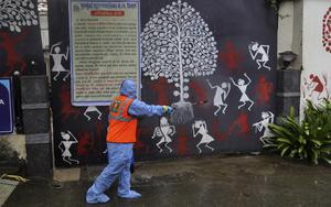 A civic worker sanitises the gate of Bollywood superstar Amitabh Bachchan's residence after the actor and his son tested positive for coronavirus and were admitted to hospital in Mumbai (Rafiq Maqbool/AP)