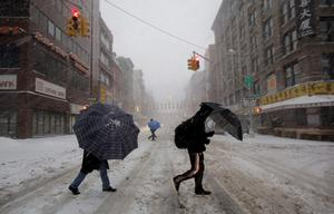 Pedestrians use umbrellas as they walk through falling snow in the Chinatown neighborhood of New York, Thursday, Feb. 13, 2014. Snow and sleet are falling on the East Coast from North Carolina to New England a day after sleet, snow and ice bombarded the Southeast. (AP Photo/Mark Lennihan)