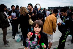 "A migrant child blows soap bubbles as hundreds of refugees wait for a bus further to Austria after crossing the Hungarian-Austrian border in Nickelsdorf on September 5, 2015. Thousands of migrants streamed into Austria from Hungary on September 5, 2015 in what Vienna called a ""wake up call"" for Europe to get to grips with its biggest refugee influx since World War II.  AFP PHOTO / VLADIMIR SIMICEKVladimir Simicek/AFP/Getty Images"