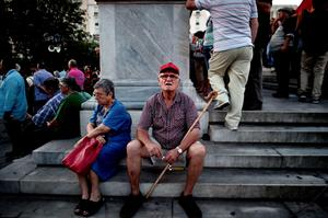 "Elderly people take a rest during a demonstration of supporters of Greece's anti-European communist party (KKE) in Athens on July 2, 2015. General Secretary of KKE called his party's supporters to vote with an invalid ballot at the referundum of July 5. The radical left government of Prime Minister Alexis Tsipras ""may very well"" resign if Greeks spurn its call to vote 'No' in the plebiscite, Finance Minister Yanis Varoufakis said. AFP PHOTO / ARIS MESSINISARIS MESSINIS/AFP/Getty Images"
