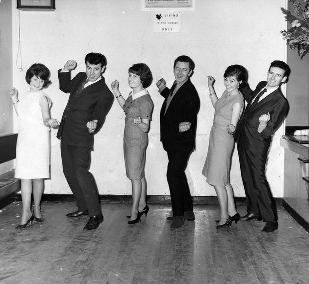 """"""" This is how you do it."""" Three Randalstown fans get some quick tuition on """"The Hucklebuck"""" from members of the Royal Showband. From left: Alice O'hara, Ballygrooby; Brendan Bowyer, Margaret O'Hara, Ballygrooby; Ed Sullivan, Betty McKeown, Hook's Lane, and Tom Dunphy.  18/2/1965"""