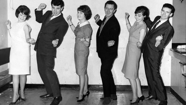 """ This is how you do it."" Three Randalstown fans get some quick tuition on ""The Hucklebuck"" from members of the Royal Showband. From left: Alice O'hara, Ballygrooby; Brendan Bowyer, Margaret O'Hara, Ballygrooby; Ed Sullivan, Betty McKeown, Hook's Lane, and Tom Dunphy.  18/2/1965"