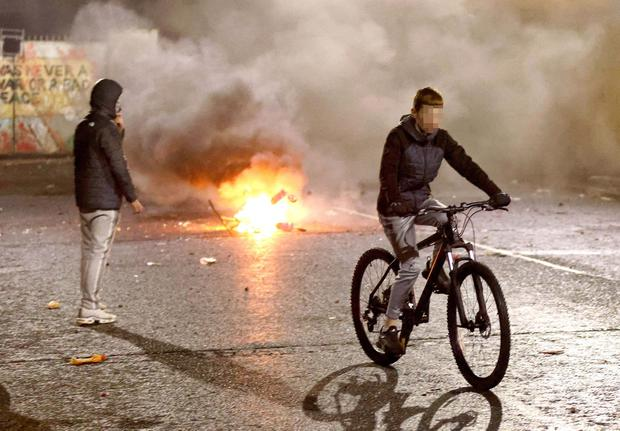 PACEMAKER, BELFAST, 7/4/2021:   A youngster cycles through the debris and petrol bombs as Loyalist and Nationalist rioters confronted each other at Lanark Way interface in Belfast on Wednesday night. Loyalists had blocked traffic during a protest which then erupted into a riot. PICTURE BY STEPHEN DAVISON