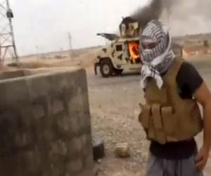 This image made from video posted by Iraqi0Revolution, a group supporting the al-Qaida breakaway Islamic State of Iraq and the Levant (ISIL) on Wednesday, June 11, 2014, which has been verified and is consistent with other AP reporting, shows a militant standing in front of a burning Iraqi Army Humvee in Tikrit, Iraq. The al-Qaida-inspired group that led the charge in capturing two key Sunni-dominated cities in Iraq this week has vowed to march on to Baghdad, raising fears about the Shiite-led governments ability to slow the assault following lightening gains. Fighters from ISIL on Wednesday took Saddam Hussein's hometown of Tikrit, as soldiers and security forces abandoned their posts and yielded ground once controlled by U.S. forces. (AP Photo/Iraqi0Revolution via AP video)