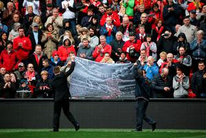 LIVERPOOL, ENGLAND - APRIL 15:  A banner is unfurled in front of supporters before a memorial service to mark the 27th anniversary of the Hillsborough disaster, at Anfield stadium on April 15, 2016 in Liverpool, England. Thousands of fans, friends and relatives will take part in the final Anfield memorial service for the 96 victims of the Hillsborough disaster. Earlier this year relatives of the victims agreed that this year's service would be the last. Bells across the City of Liverpool will ring out during a one minute silence in memory of the 96 Liverpool supporters who lost their lives during a crush at an FA Cup semi-final match against Nottingham Forest at the Hillsborough football ground in Sheffield, South Yorkshire in 1989.  (Photo by Christopher Furlong/Getty Images)