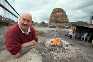 Former Bonfire builder Colin Tweedie, poses for a photograph beside a bonfire in the village area of Belfast, Northern Ireland on July 10, 2017, ahead of the traditional 11th night bonfires. [Photo: Paul Faith/AFP/Getty Images]