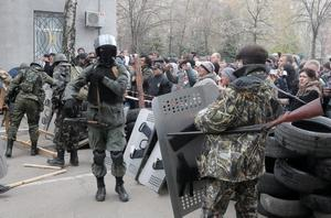 Armed pro-Russian activists occupy the police station carrying riot shields as people watch on, in the eastern Ukraine town of Slovyansk on Saturday, April 12, 2014