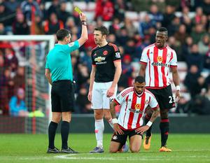 SUNDERLAND, ENGLAND - FEBRUARY 13:  Michael Carrick of Manchester United is shown a yellow card by referee Andre Marriner after fouling Yann M'Vila of Sunderland during the Barclays Premier League match between Sunderland and Manchester United at the Stadium of Light on February 13, 2016 in Sunderland, England.  (Photo by Clive Brunskill/Getty Images)