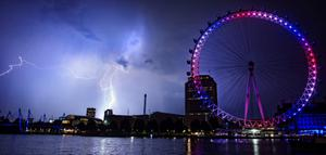 Lightning strikes behind The London Eye in central London which is coloured red, white and blue to mark the birth of a baby boy, at 4.24pm yesterday to the Duke and Duchess of Cambridge at St Mary's Hospital.  Lewis Whyld/PA Wire