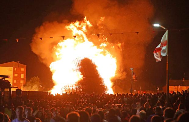 """The huge bonfire in the loyalist Corcrain area of Portadown, Co Armagh, is lit on the """"Eleventh night"""" to usher in the Twelfth commemorations. Picture date: Sunday July 11, 2021. PA Photo. Loyalists across Northern Ireland have been building bonfires in preparation for the eleventh night celebrations, as part of a tradition to mark the anniversary of the Protestant King William's victory over the Catholic King James at the Battle of the Boyne in 1690.  See PA story ULSTER Twelfth. Photo credit should read: Niall Carson/PA Wire"""