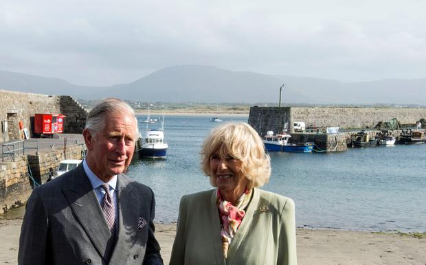 """Britain's Prince Charles, Prince of Wales (L) and his wife Camilla, Duchess of Cornwall (R) visit the harbour in the village of Mullaghmore in Ireland on May 20, 2015 where the prince's great-uncle Lord Mountbatten was killed in an IRA explosion in 1979. Britain's Prince Charles spoke of his """"anguish"""" at the murder of his godfather by IRA paramilitaries in 1979 as he became the first royal to visit the assassination site in Ireland.  Charles remembered Lord Louis Mountbatten as """"the grandfather I never had"""" on an emotional trip to the rugged coastline, saying he understood the suffering of the Irish people in """"a profound way"""".  Peter McHugh helped with the rescue effort in the aftermath of the 1979 attack.  AFP PHOTO / POOL / ARTHUR EDWARDSARTHUR EDWARDS/AFP/Getty Images"""