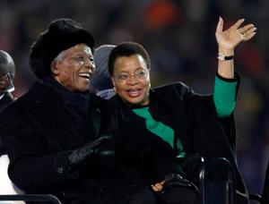 FILE - In this July 11, 2010 file photo, former South African President Nelson Mandela, left, sits next to his wife, Graca Machel, as they are driven across the field ahead of the World Cup final soccer match between the Netherlands and Spain at Soccer City in Johannesburg, South Africa.   South Africa's president Jacob Zuma says, Thursday, Dec. 5, 2013, that Mandela has died. He was 95.  (AP Photo/Luca Bruno, File)