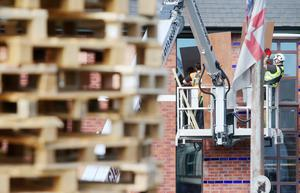 Workmen board up windows of property beside a bonfire at the end of the Comber Greenway off Ravenscroft Avenue in east Belfast.  Picture by Jonathan Porter/PressEye.com